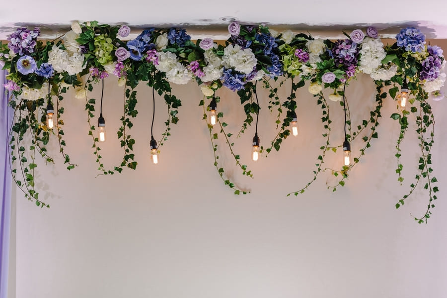 Beautiful decor made with garland with luminous lamps and floral decorations. Decor of flowers on wedding ceremony.