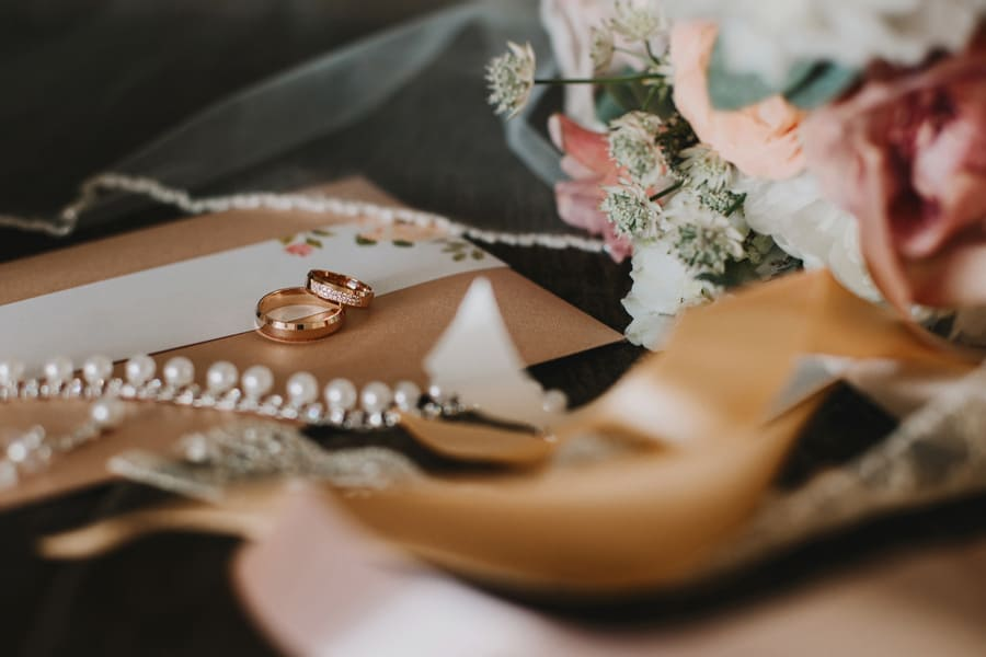 Two gold wedding rings with gemstones are among the accessories: bridal bouquet, cards, veils and lace ribbons.